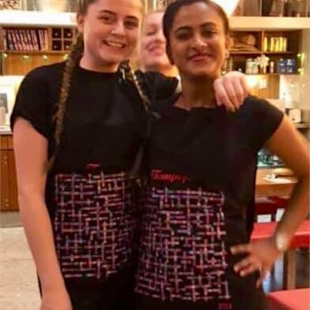 photo of girls wearing tampopo name-chains aprons